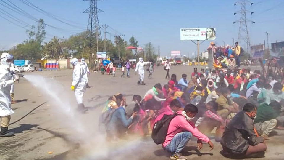 A screen grab shows healthcare workers, in protective suits, spray a solution through hose pipe on migrants before allowing them to enter the town of Bareilly, Monday, March 30, 2020. The migrants reached the town due to the nationwide complete lockdown imosed to limit the spread of coronavirus.