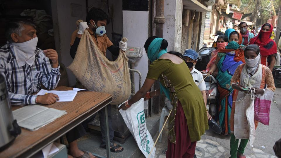 People queue up to take foodgrains from a government PDS shop in Delhi on day 6 of the 21-day nationwide lockdown to check the spread of coronavirus.