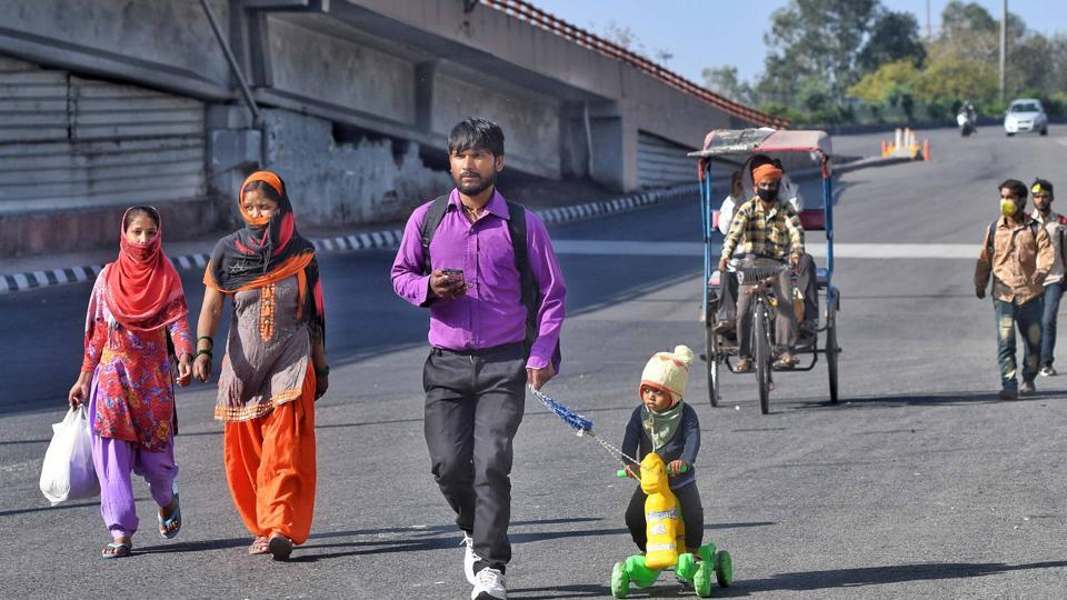 Ranjit Rajput, 28, a migrant worker from Bareilly walks with his son Prince, 4, to their native state on Day 4 of the 21 day nationwide lockdown -- to check the spread of coronavirus, at Ashram.