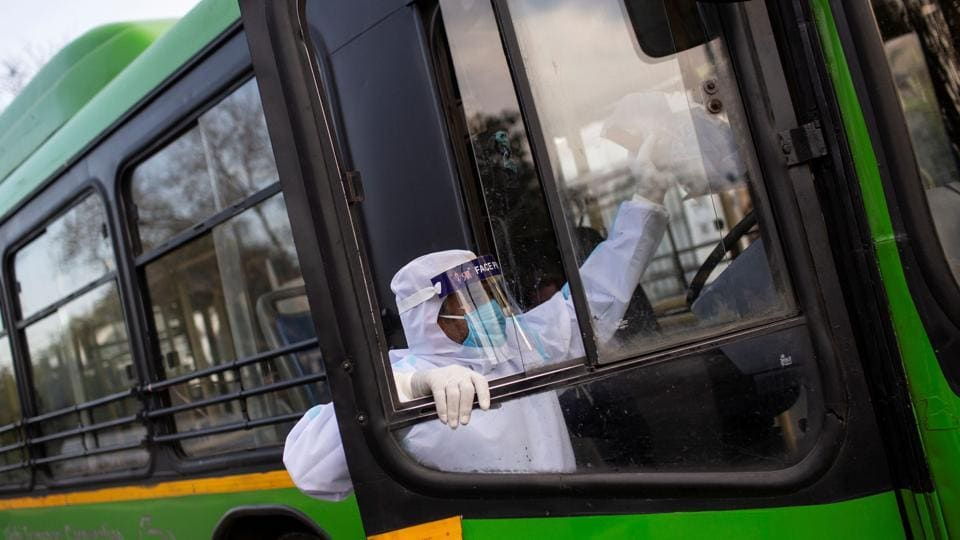 A driver wearing a protective suit climbs a bus used for transporting suspected carriers of coronavirus to a quarantine facility amid concerns about the spread of coronavirus disease (COVID-19), in Nizamuddin area of New Delhi.