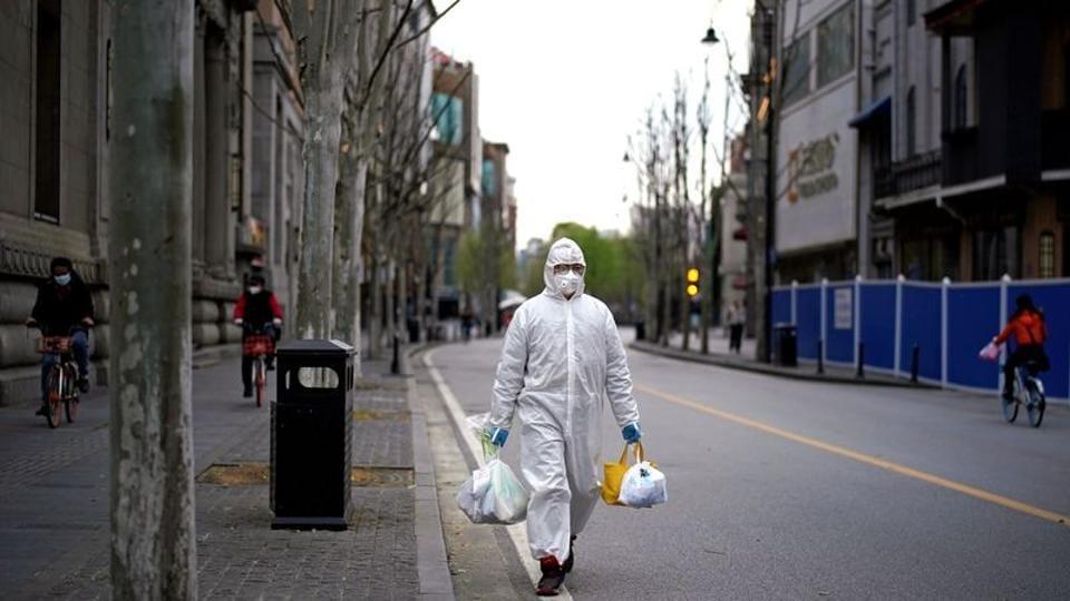 A man wearing a hazmat suit walks on a street in Wuhan, Hubei province of China amid coronavirus outbreak.