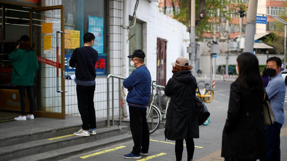 People practise social distancing as they queue to enter a supermarket as the spread of coronavirus disease (COVID-19) continues in Beijing, China.