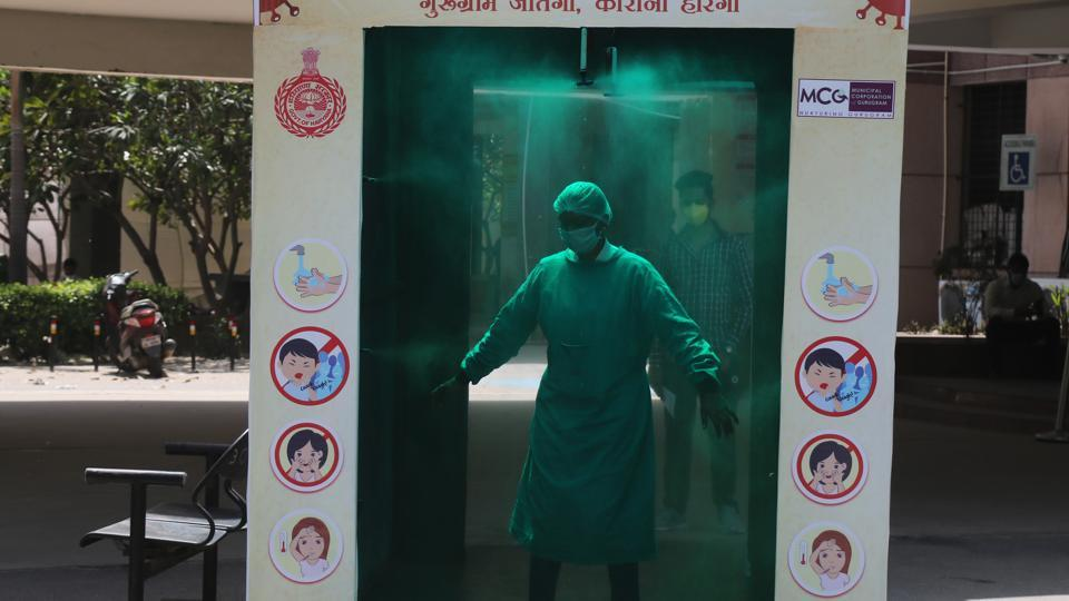 A medical staff in protective gear walks through a disinfection tunnel outside Civil Hospital Sector 10, on day fourteen of the 21-day nationwide lockdown to curb the spread of Coronavirus  in Gurugram on  April 7, 2020.