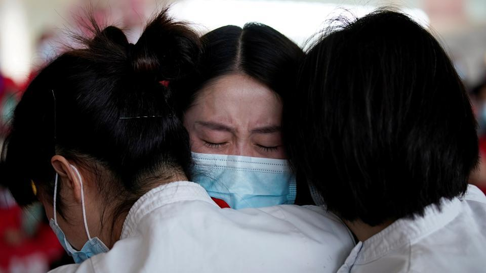 Medical workers hug at Tianhe International Airport after travel restrictions to leave Wuhan, the capital of Hubei province and China's epicentre of the novel coronavirus disease Covid-19 outbreak, were lifted, on April 8.