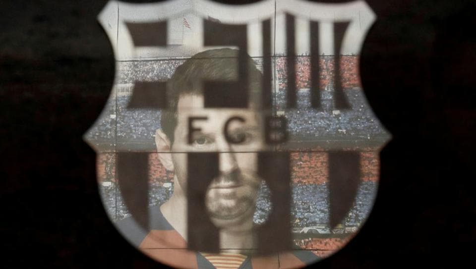 A picture of Lionel Messi is reflected in the Barcelona emblem outside the stadium