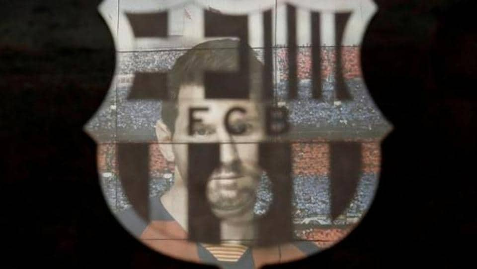 A picture of Lionel Messi is reflected in the Barcelona emblem outside the stadium before a match.