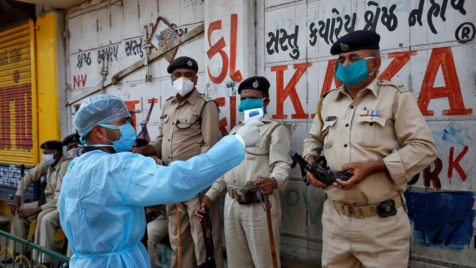A paramedic uses an infrared thermometer to measure the temperature of a police officer alongside a road during a 21-day nationwide lockdown to slow the spreading of coronavirus disease (COVID-19) in Ahmedabad.