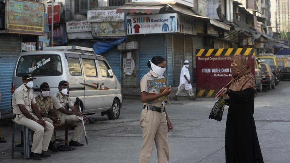A police officer stops a woman in Dharavi, one of Asia's largest slums, during lockdown to prevent the spread of the new coronavirus in Mumbai.