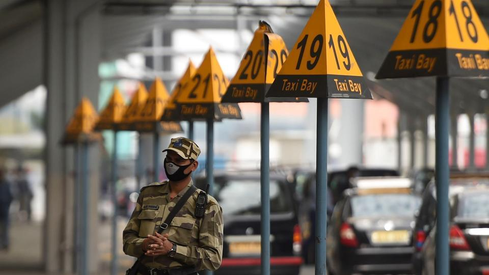 A security personnel wearing a facemask amid concerns over the spread of the COVID-19 novel coronavirus, stands guard outside at the Indira Gandhi International Airport in New Delhi.