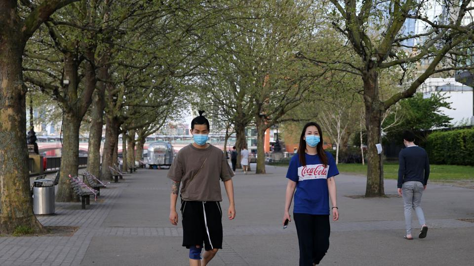 Peopla wearing protective face masks walk on the south bank in London on April 12, 2020, during the nationwide lockdown to combat the novel coronavirus pandemic. - Britain's coronavirus death toll has passed 10,000, after another 737 people died from the virus in the latest count, the health ministry said on Sunday.