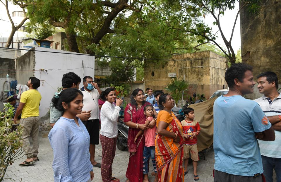 People gather outside their houses after the earthquake measuring 3.5 on the Richter scale, near Mandi House, in New Delhi.