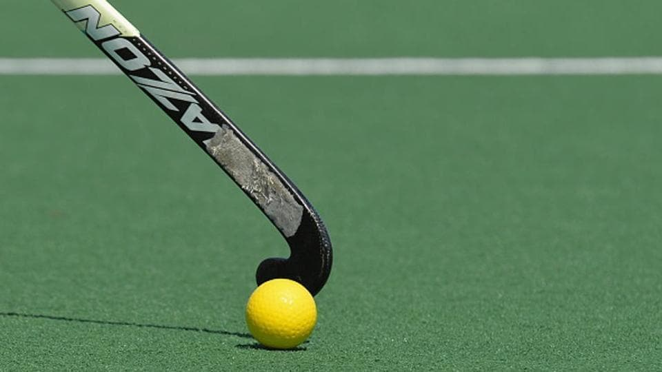 A field hockey stick hits the ball