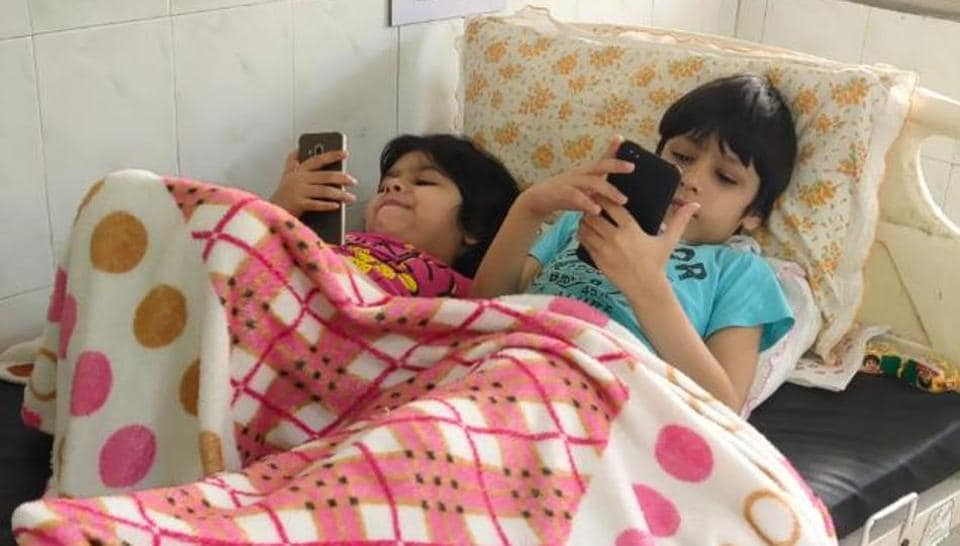 Eight-year-old Arush (right) and his sister Aaina, 6, playing games on mobile phones during their time in the isolation ward of Sirsa civil hospital.