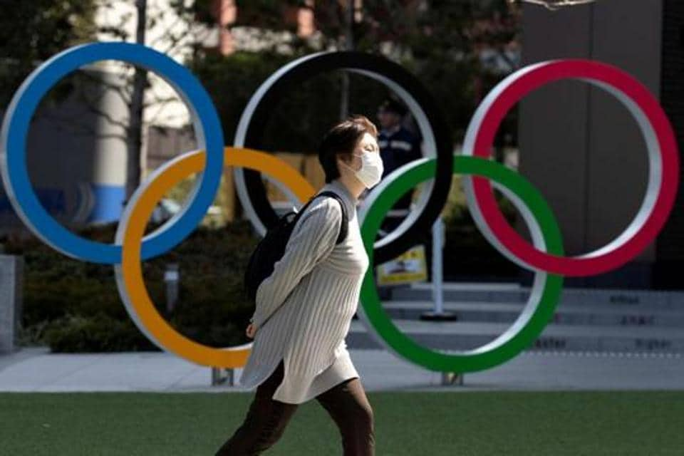 A woman wearing a protective face mask, following an outbreak of the coronavirus disease (COVID-19), walks past the Olympic rings in front of the Japan Olympics Museum in Tokyo.