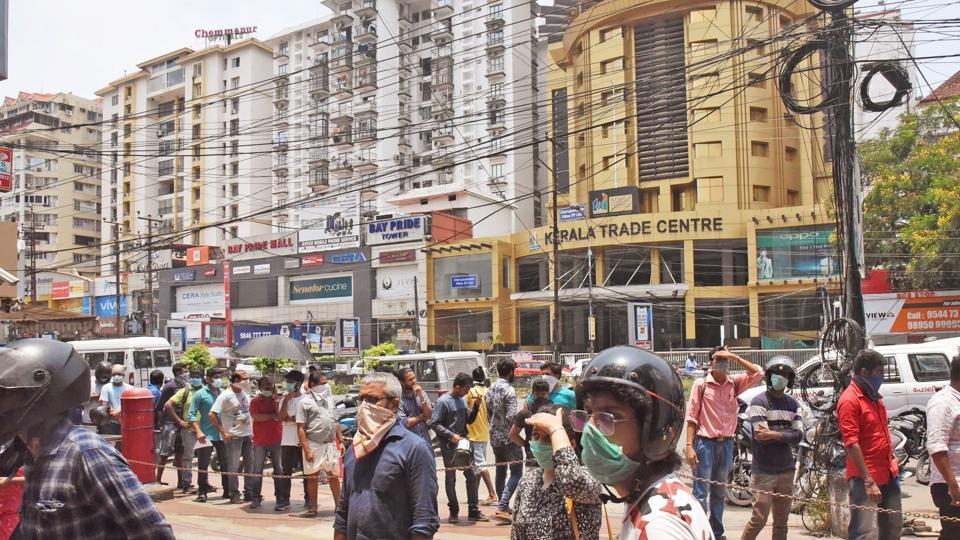 People waiting in front of a mobile phone shopping complex for purchasing and repairing mobile phones during the nationwide lockdown in wake of coronavirus pandemic, in Kochi on Sunday. (ANI Photo)