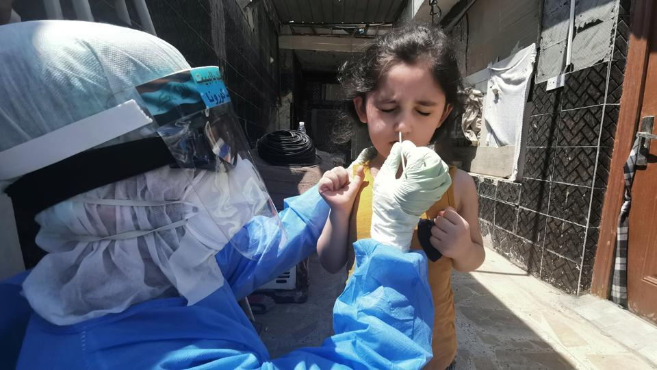 A member of a medical team that works with mobile coronavirus disease (COVID-19) testing units wears protective gear as he takes a swab from a child to track new cases of COVID-19, in Najaf, Iraq April 21,2020. Picture taken April 21,2020. REUTERS/Ahmed Saed