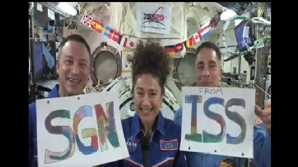 Astronauts holding placards of Some Good News(SGN) from ISS.