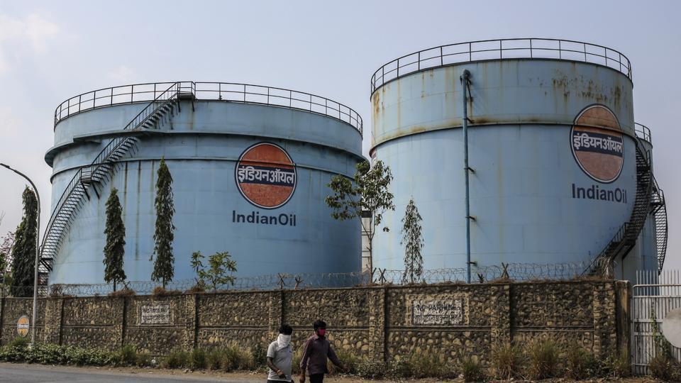 Pedestrians walk along a road past storage tanks in a Indian Oil Corp. facility near Jawaharlal Nehru Port, operated by Jawaharlal Nehru Port Trust (JNPT), in Navi Mumbai, Maharashtra.