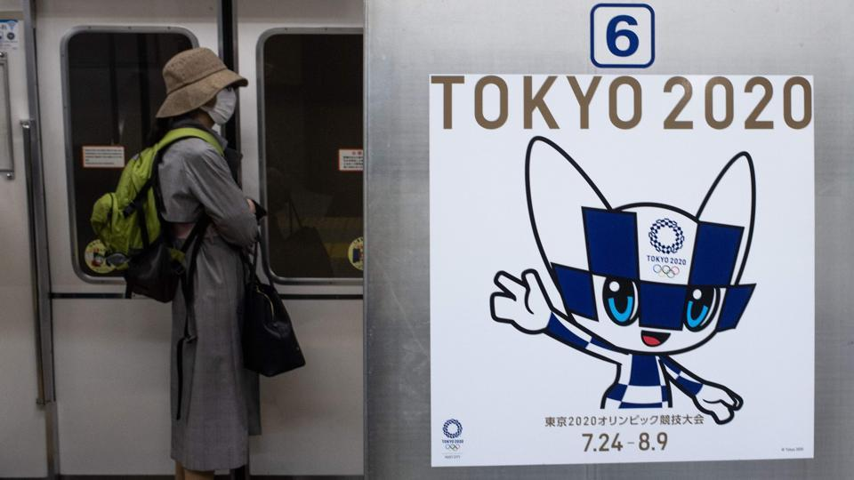 A passenger wearing a face mask stands next to a poster of Tokyo 2020 Olympic mascot Miraitowa.