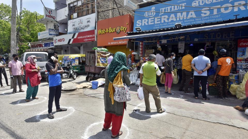 Residents wait inside marked circles to maintain distance to buy groceries at Munirka Market during lockdown to curb spread of coronavirus in New Delhi on Saturday April 25, 2020.