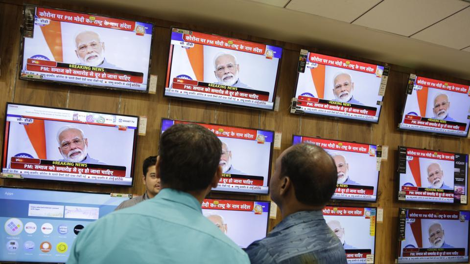 People watch Prime Minister Narendra Modi address the nation in a televised speech about Covid-19 situation, at an electronics store in Ahmedabad, India.