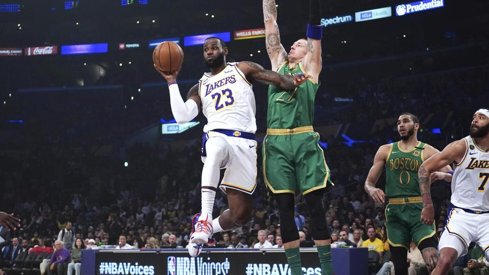 Los Angeles Lakers forward LeBron James (23) passes the ball under pressure from Boston Celtics center Daniel Theis (27) in the first half at Staples Center.