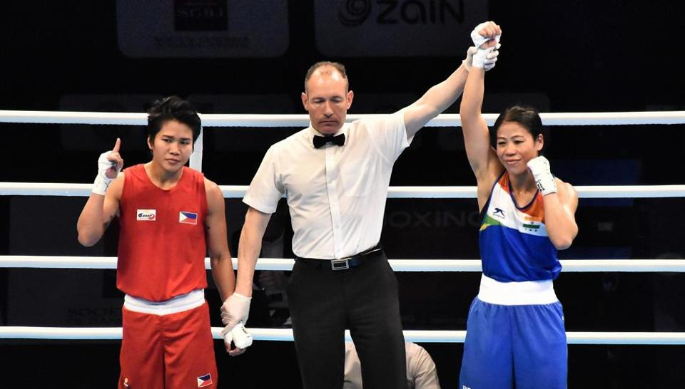 Referee raises the hand of boxer Mary Kom after winning her quarter final bout.