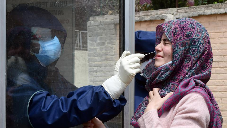 A healthcare worker collects a swab sample of a woman for Covid-19  test in Srinagar on Monday.