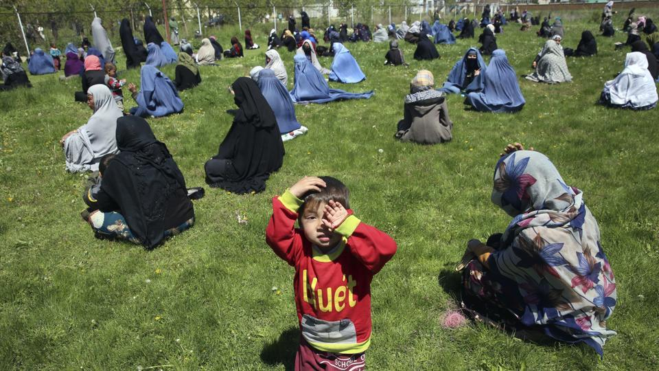 Afghans wait to receive free wheat donated by the Afghan government ahead of the upcoming Muslim holy fasting month of Ramadan, during a quarantine for the coronavirus, in Kabul, Afghanistan.