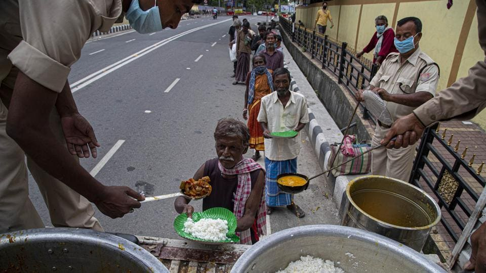 Homeless people line up for free food distributed by Police during lockdown to curb the spread of new coronavirus, in Gauhati, India.
