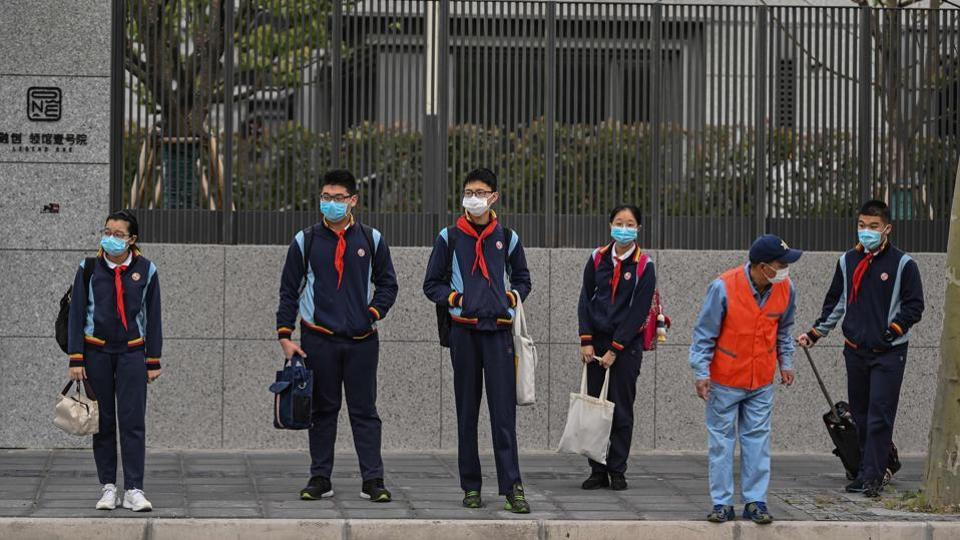 Students wearing face masks arrive at the Huayu Middle School in Shanghai on April 27, 2020.