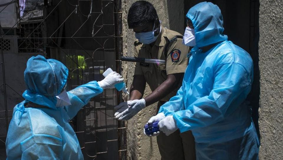 Healthcare workers helps to sanitise a policeman during a nationwide lockdown to slow the spreading of the coronavirus disease  at Dharavi in Mumbai.