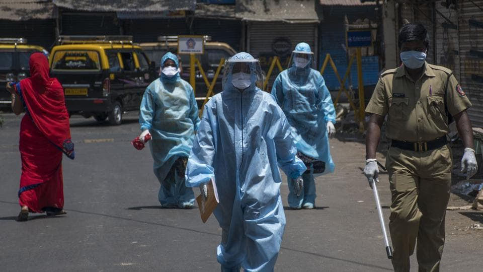 Healthcare workers walk on the road towards residential area to check residents for Covid-19 during a nationwide lockdown to slow the spreading of the coronavirus in Dharavi in Mumbai, on Monday, April 27, 2020.