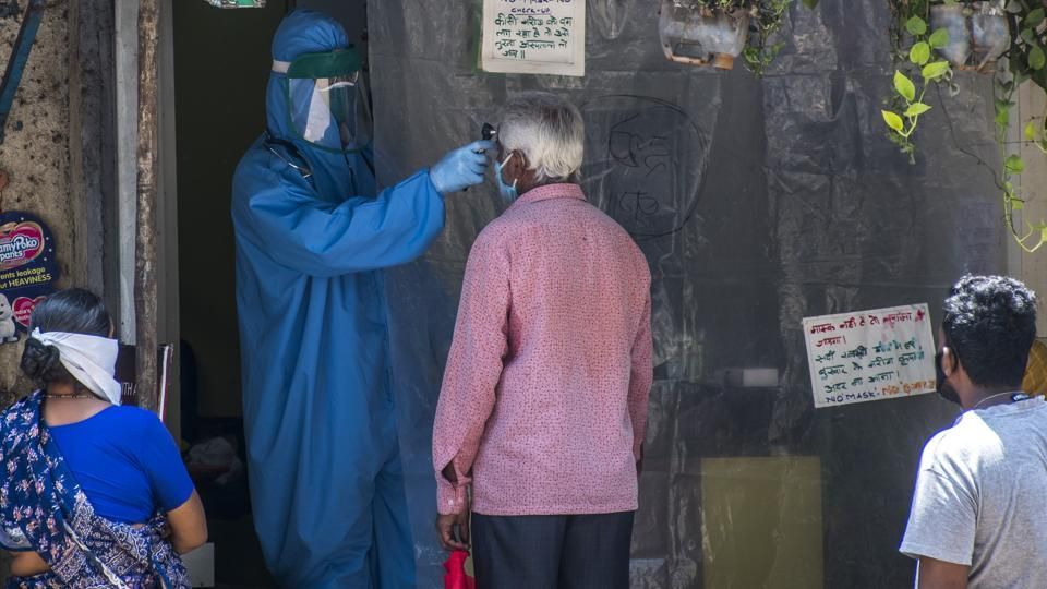 A doctor checks the temperature of patients at Mumbai's Dharavi, on Monday.