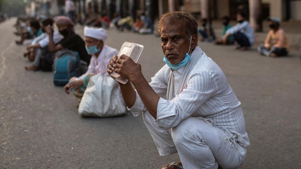 A daily wage labourer waits to receive free food during an extended nationwide lockdown to slow the spread of the coronavirus disease (COVID-19) in New Delhi, India.