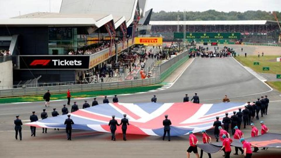 General view of a Union Jack flag being carried out on to the track by service personnel before the race.