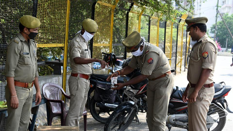 Lucknow Police personnel clean a food packet, during lockdown to curb the spread of coronavirus, at Daliganj, in Lucknow, Uttar Pradesh, India, Tuesday, 28, 2020.