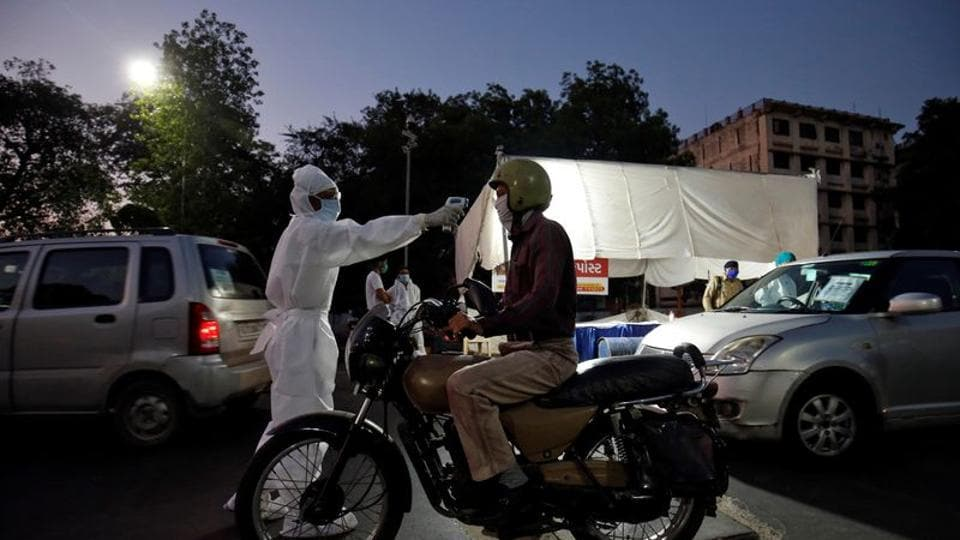 A health worker uses an infrared thermometer to measure the temperature of a motorcyclist on a road during a nationwide lockdown to slow the spreading of the coronavirus disease (COVID-19) in Ahmedabad, India.