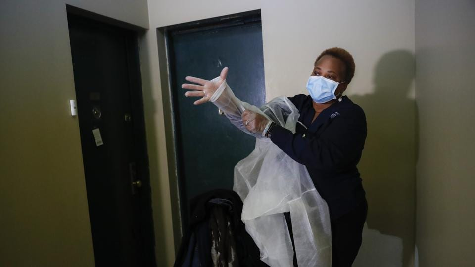 In this Thursday, April 23, 2020 photo, Ruth Caballero, a nurse with The Visiting Nurse Service of New York, puts on personal protective equipment before entering a patient's apartment as she makes her rounds in upper Manhattan in New York. )