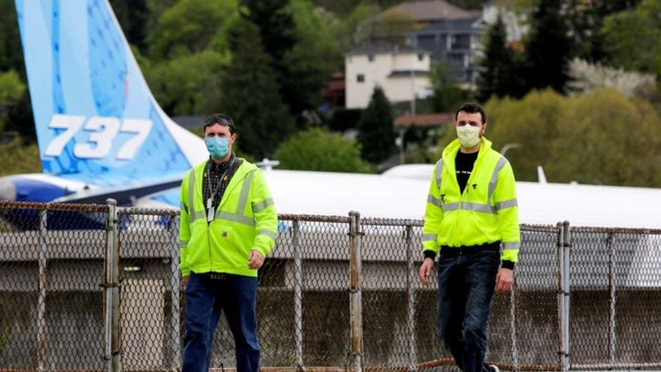 Boeing workers wear masks at the Boeing Renton Factory, where 737 MAX airliners are manufactured, as commercial airplane production resumes following a suspension of operations last month in response to the coronavirus pandemic.