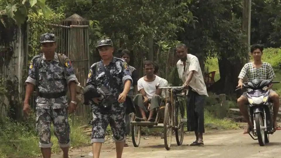 Myanmar Border Guard Police walk ahead of a trishaw driver and passenger along the main road of Buthidaung, northern Rakhine state of Myanmar, on September 6, 2017.