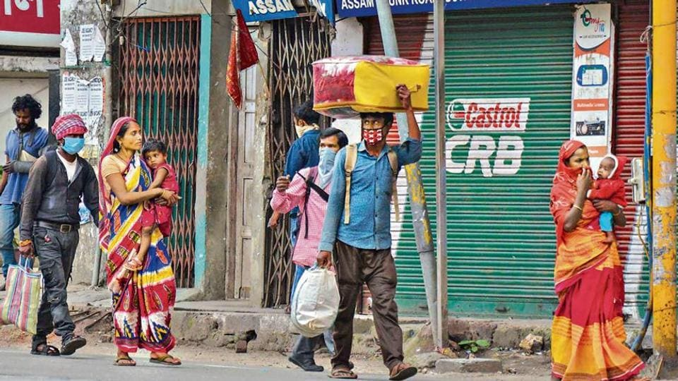 Migrant workers carrying their luggage walk towards their villages in Guwahati on Tuesday.