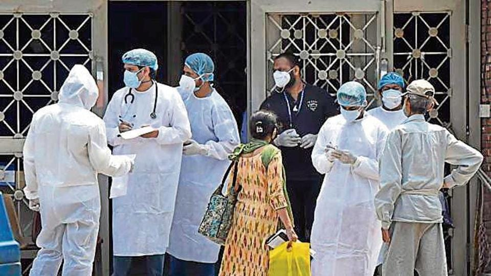 Doctors and other medical staff of Lok Nayak hospital attend to people outside the main building.