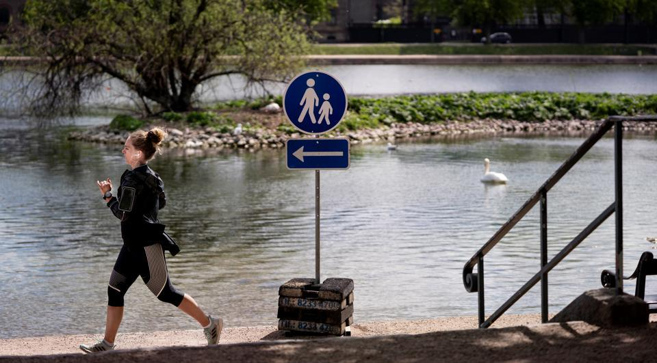 A woman runs during the spread of the coronavirus disease (Covid-19) when it is permitted to run only in one direction at the Lakes, in Copenhagen, Denmark, April 28, 2020.
