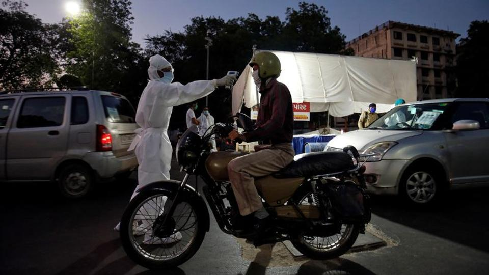 A health worker uses an infrared thermometer to measure the temperature of a motorcyclist on a road during a nationwide lockdown to slow the spreading of the coronavirus disease (COVID-19) in Ahmedabad.