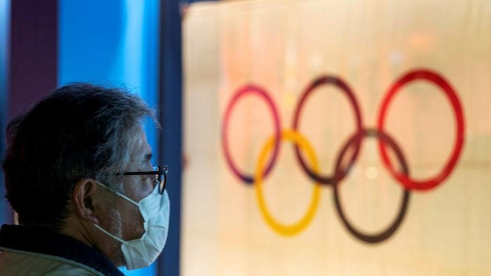 FILE PHOTO: A man wearing a protective face mask, following an outbreak of the coronavirus, stands in front of The Tokyo Olympic flag 1964 at The Japan Olympics museum in Tokyo, Japan, February 26, 2020. REUTERS/Athit Perawongmetha