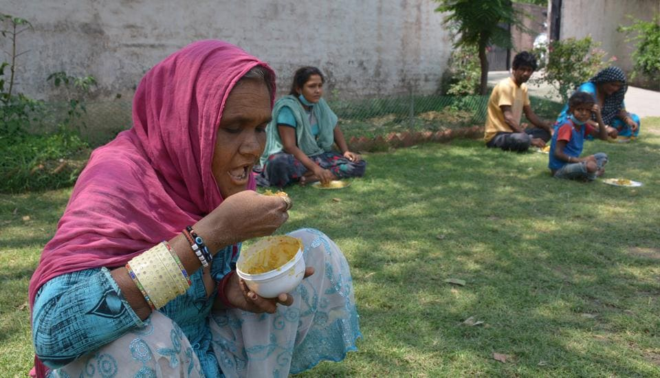 Migrant workers eating lunch at a temporary shelter home in Sector 20, Panchkula.