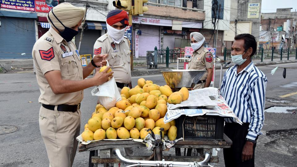 Punjab police officers buying fruits from a street vendor during government imposed nationwide lockdown as a preventive measure against the Coronavirus, in Jalandhar on Tuesday.