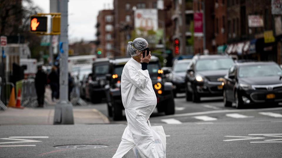 A pregnant woman wearing a hazmat suit and a mask walks in the streets in the Elmhurst neighbourhood of Queens on April 27, 2020 in New York City.