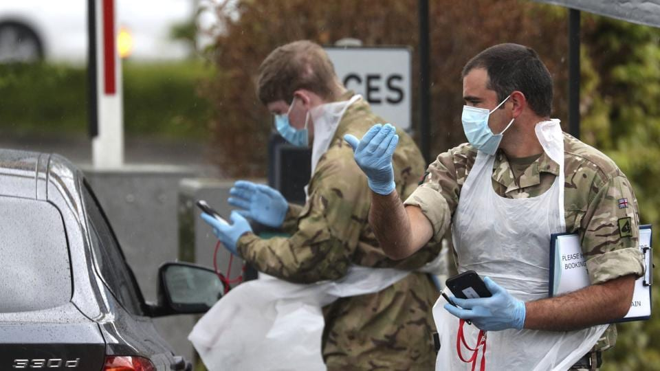 Soldiers provide instructions to people arriving at a Covid-19 testing centre in a Park and Ride facility in Salisbury, England, as the lockdown to help curb the spread of coronavirus continues.